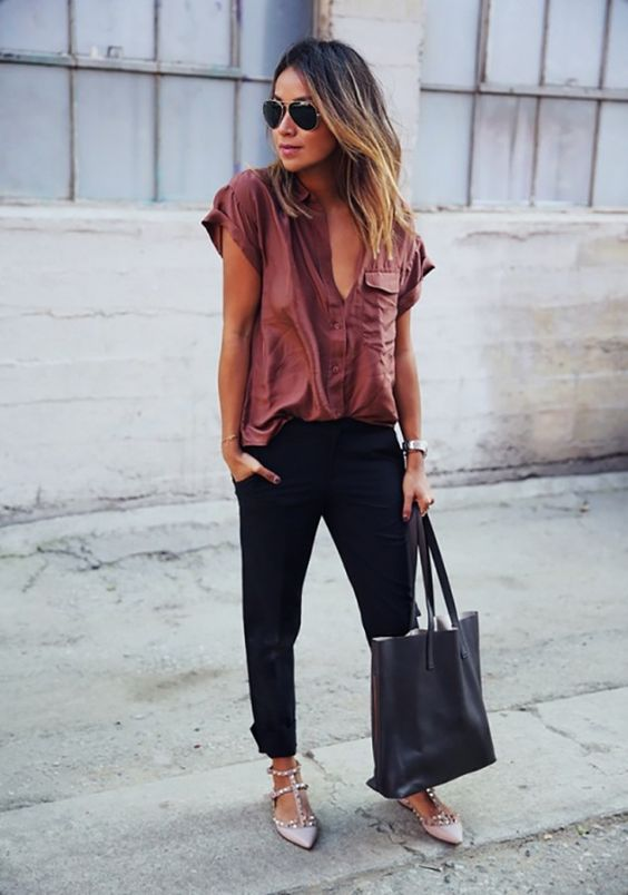 black pants, a mauve shirt, nude studded flats and a black bag