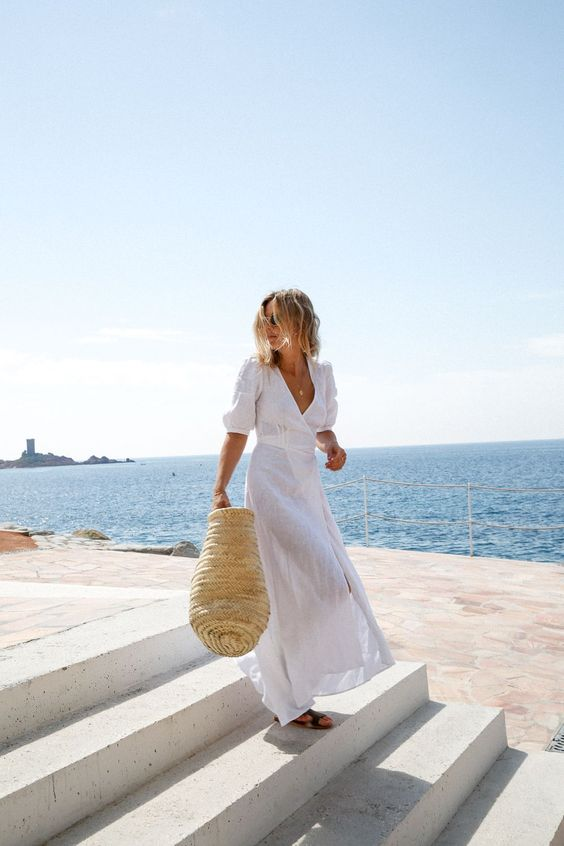 a white maxi dress with long sleeves and a deep V-neckline plus a highlighted waist