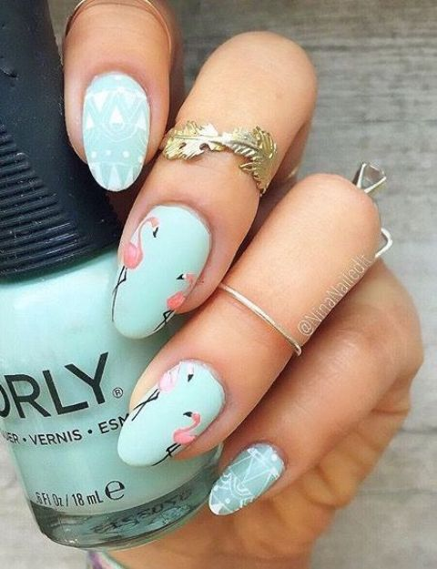mint nails - some with pink flamingos and some with white patterns on them