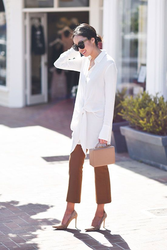 rust-colored pants, nude heels and a long white shirt with draping for a summer work look