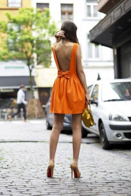 With beige pumps and golden bag