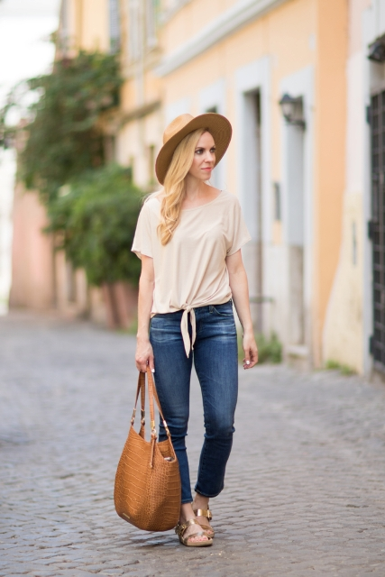 With beige shirt, wide brim hat, jeans and brown bag