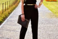 With black jumpsuit, platform sandals and black clutch