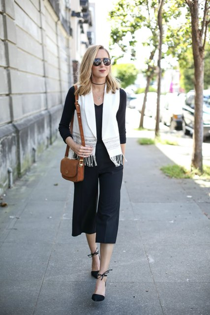 With black shirt, brown small bag, black culottes and black ankle strap shoes