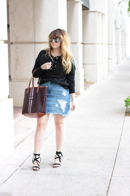With black shirt, lace up sandals and printed tote