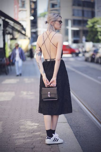 Open back dress with a black small bag and a pair of white and black sneakers are perfect to show off tattoos