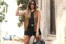 With black top, black shorts, ankle boots and leather bag
