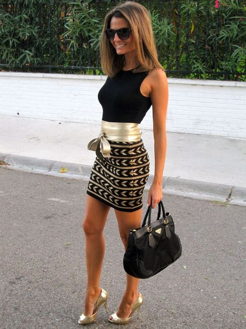 With black top, printed skirt, golden pumps and black bag