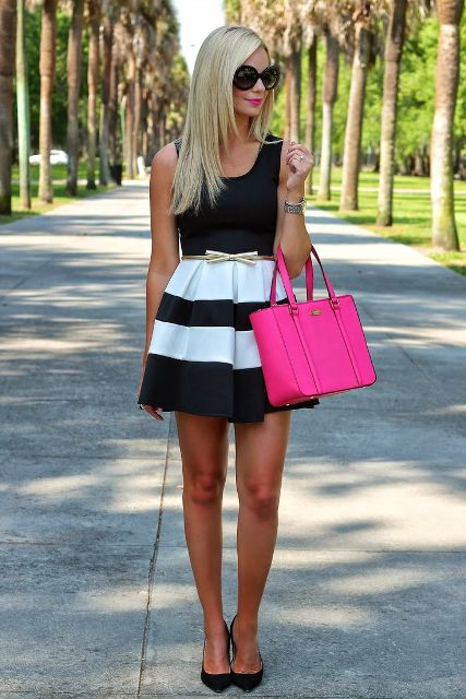 With black top, striped skater skirt, hot pink bag and black shoes
