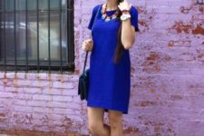 With blue dress, necklace and bag