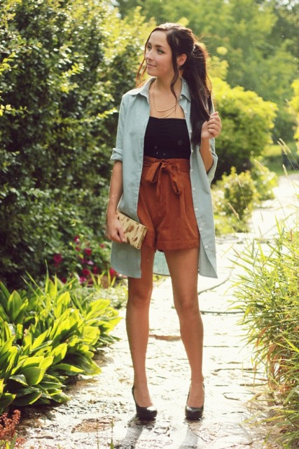 With button down long shirt, high-waisted shorts, clutch and pumps