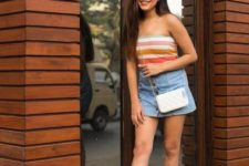 With denim mini skirt and white chain strap bag