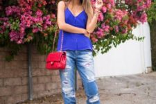 With distressed cuffed jeans, red sandals and red bag