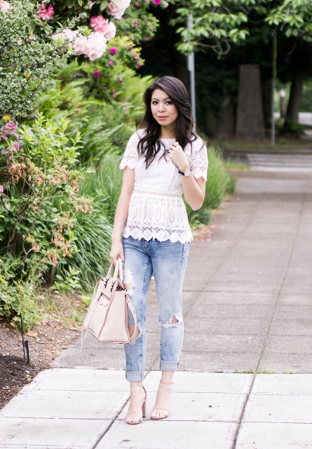With distressed jeans, beige shoes and beige bag