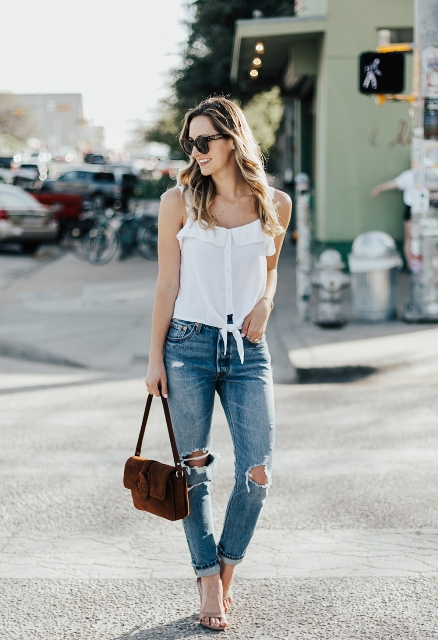 With distressed jeans, brown velvet bag and high heels