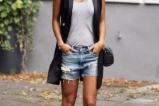 With gray shirt, lace up flats, black long vest and mini bag