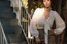 With high-waisted skirt and brown bag