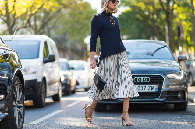 With navy blue shirt, pleated skirt and black bag