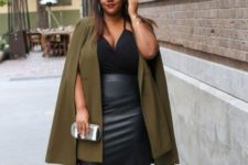 With olive green cape, black leather skirt, lace up sandals and clutch