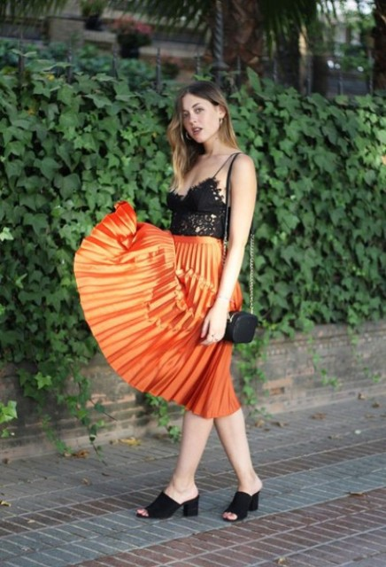 With orange pleated skirt, black mules and black mini bag