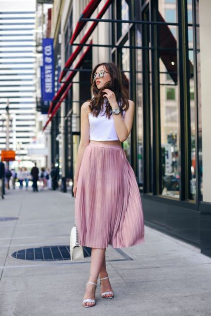 With pink pleated midi skirt, white sandals and white chain strap bag