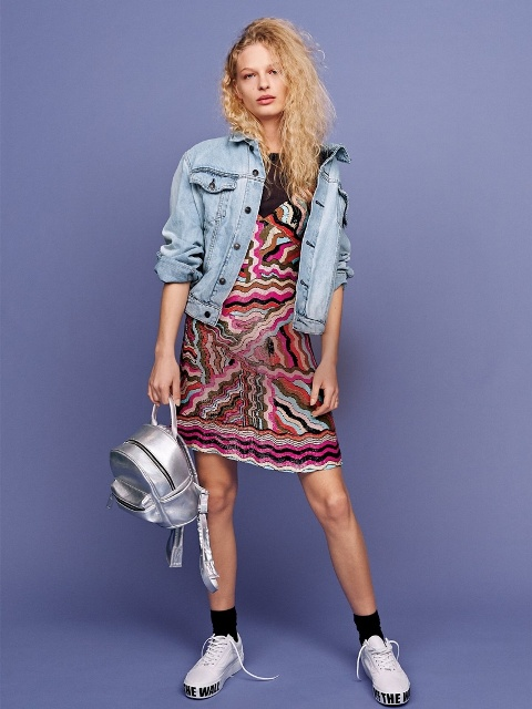A mini metallic backpack with a printed dress, denim jacket and white sneakers