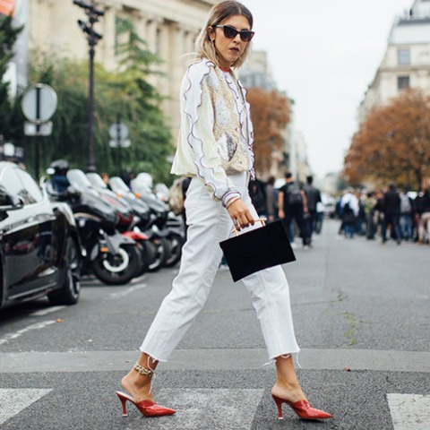 With printed ruffled shirt, white crop pants and black bag