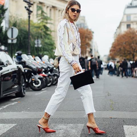With printed ruffled shirt, white crop pants and black bag