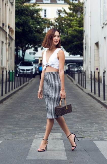 With printed skirt, black high heels and printed mini bag