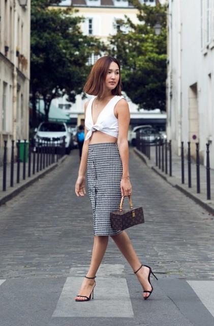 With printed skirt, black high heels and printed mini bag