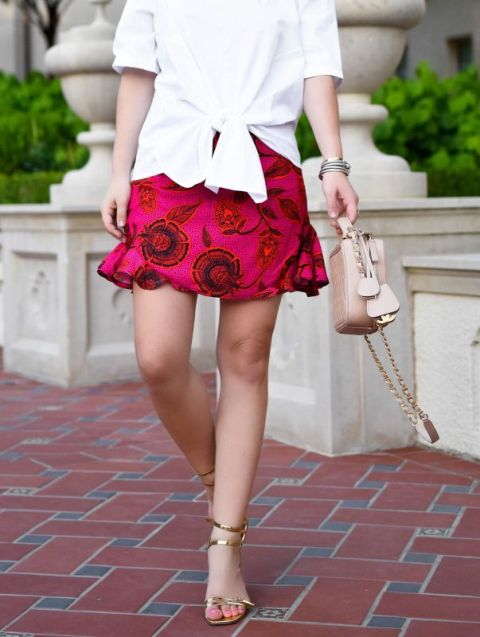 With red floral skirt, golden shoes and pale pink bag