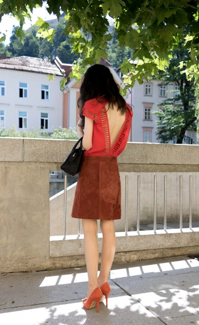 With suede skirt, black bag and orange pumps