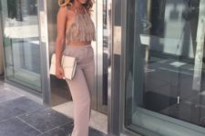 With trousers, high heels and beige clutch