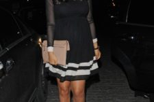With white and black dress and beige clutch