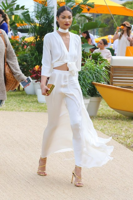 With white maxi skirt, golden sandals and golden mini clutch