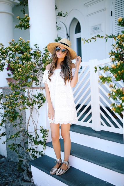 With white off the shoulder dress and wide brim hat