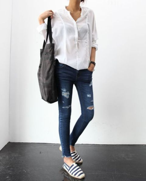 With white shirt, black tote and distressed jeans