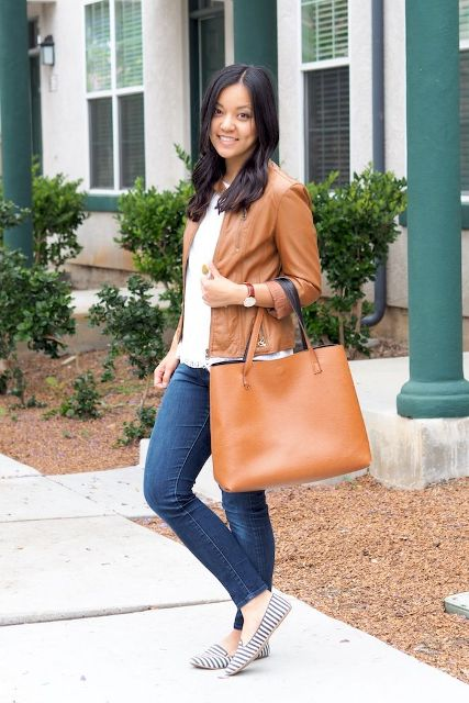 With white shirt, brown leather jacket, skinny jeans and brown tote