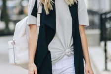 With white shorts, black long vest and white backpack