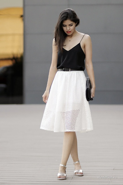 With white skirt, silver sandals and clutch