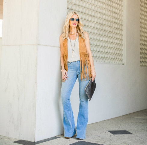 With white top, flare jeans, platform shoes and black clutch