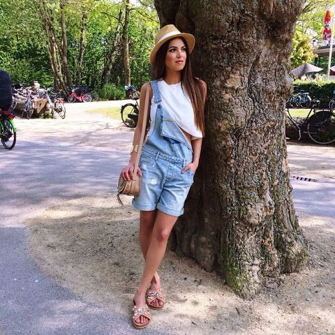With white top, wide brim hat, beige bag and flat sandals