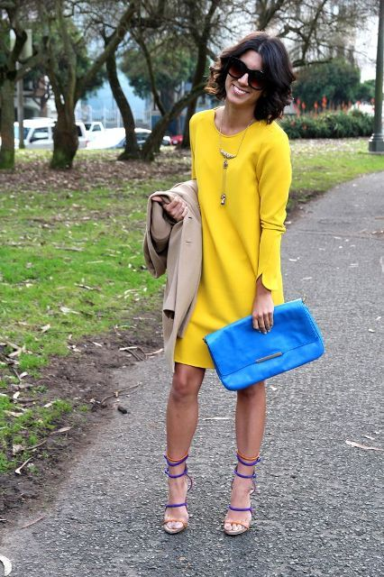 With yellow dress, blue clutch and beige coat