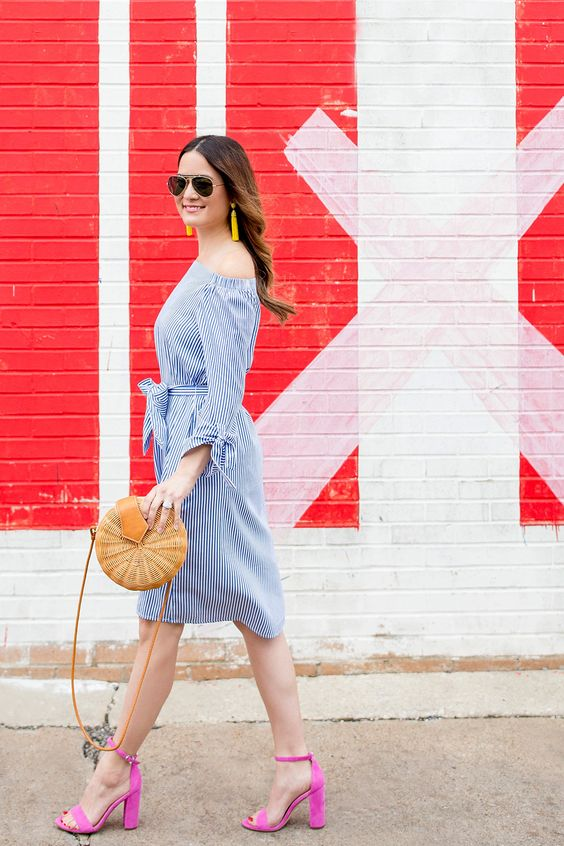 a blue striped knee dress, hot pink heels, yellow tassel earrings and a round wicker bag