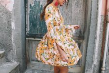 a cute mini dress with a yellow floral print, log sleeves, neutral lace up shoes and tassel earrings