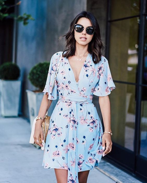 e87f6a14e0 a flattering light blue floral mini dress with short sleeves and a straw  bag for a