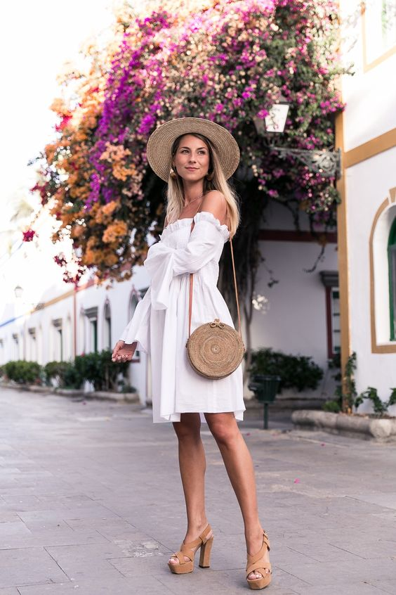 a white off the shoulder knee dress, tan heels, a hat and a round wicker bag