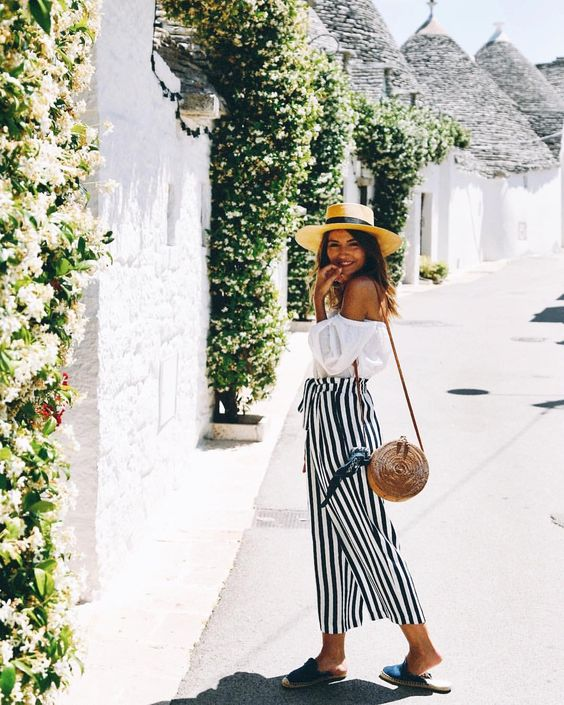a white off the shoulder blouse, a striped maxi skirt, black slippers, a hat and a round wicker bag