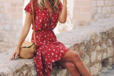 07 a red printed dress with a lace up bodice, short sleeves, a wide brim hat and tan shoes
