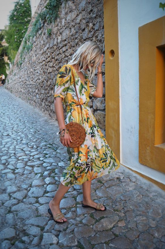 a tropical print midi wrap dress, flats and a round wicker bag